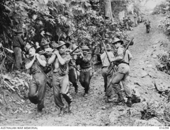 Stretcher bearers carrying a wounded mate down along a muddy track north of Gusika while men of militia 29th/46th Battalion plod up a steep grade on their way to contact the Japanese.